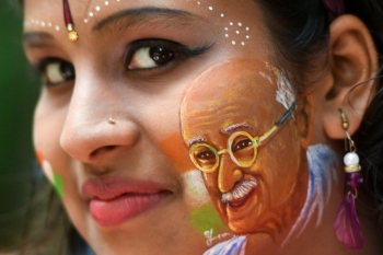 A girl poses for a picture with her face painted depicting a portrait of India's independence hero Mahatma Gandhi as the country celebrates its 73rd Independence Day, which marks the end of British colonial rule, in Bangalore on Thursday. — AFP