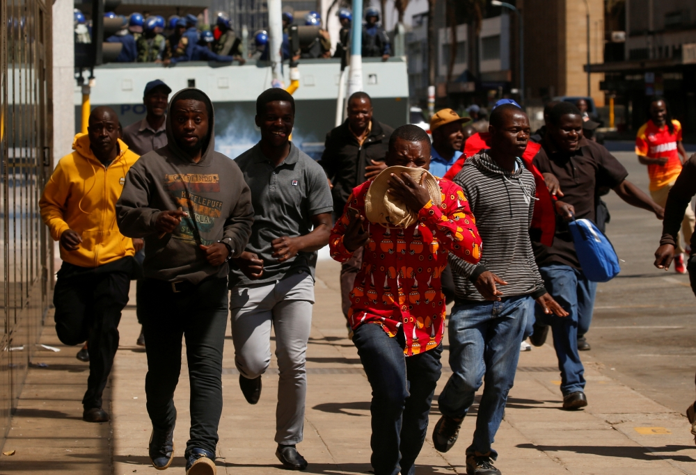 Protesters flee from teargas during clashes after police banned planned protests over austerity and rising living costs called by the opposition Movement for Democratic Change (MDC) party in Harare, Zimbabwe, on Friday. -Reuters