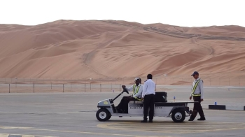 In this file photo, Aramco staff members stand on the tarmac at the Saudi Aramco airport surrounded by sand dunes by the Shaybah oilfield, some 800 km southeast of the eastern oil center of Dhahran. — AFP