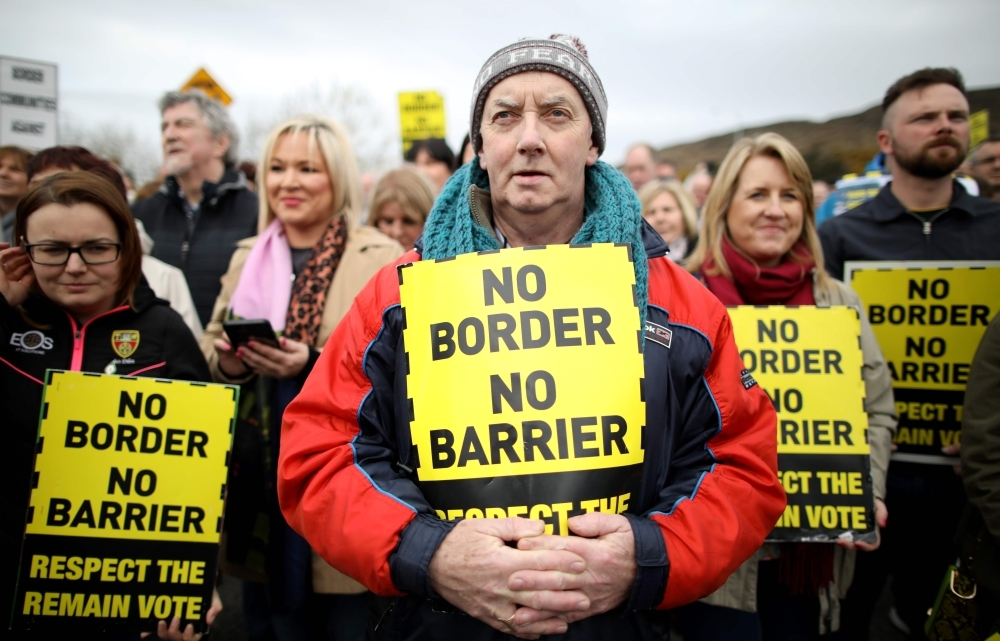 Protesters against any border between Ireland and Northern Ireland because of Brexit hold placards at the Carrickcarnan border between Newry in Norther Ireland and Dundalk in the Irish Republic in this March 30, 2019 file photo. — AFP