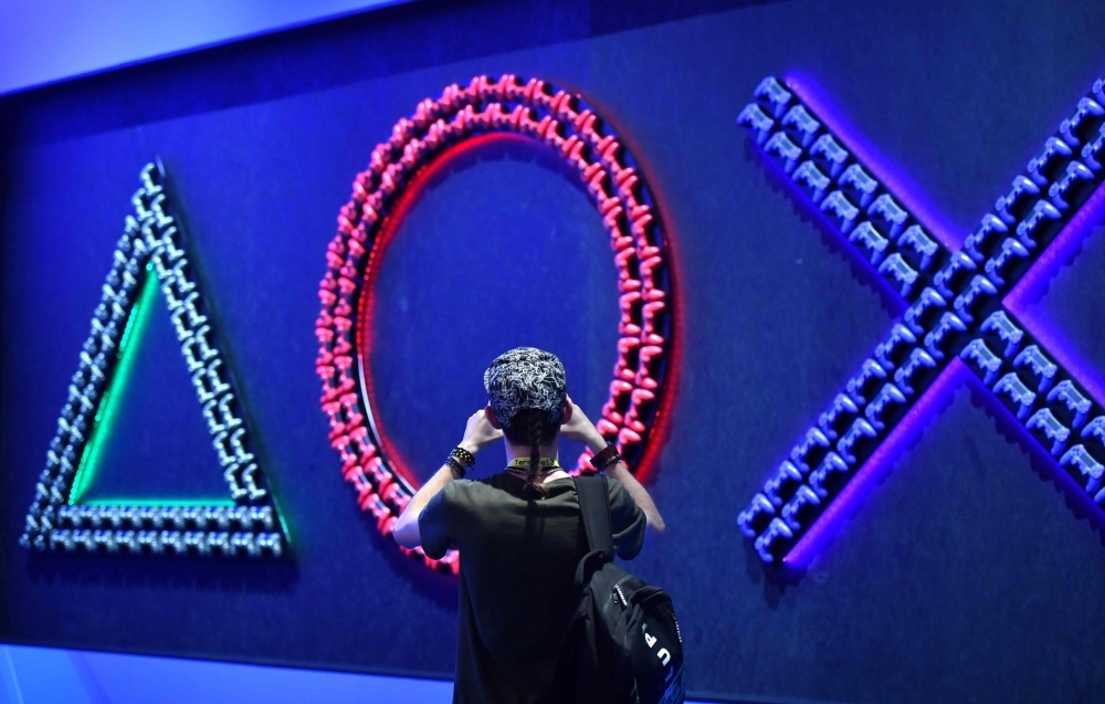 A man takes a picture of game consoles at the stand of Playstation during the media day of the Gamescom video games trade fair in Cologne, western Germany, on Tuesday. — AFP