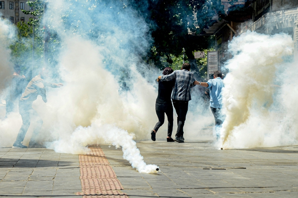 Turkish anti-riot police officers use tear gas to disperse demonstrators during a protest against the replacement of Kurdish mayors with state officials in three cities, in Diyarbakir, Turkey, on Tuesday.  — AFP