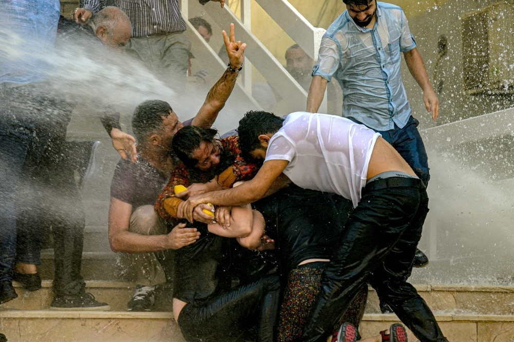 Demostrators protect each other as they are hit by water cannon during a protest against the replacement of Kurdish mayors with state officials in three cities, in Diyarbakir, in eastern Turkey, on Tuesday. — AFP