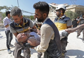 Members of the Syrian Civil Defense (White Helmets) carry an injured man after removing him from under the rubble of a building that collapsed during reported airstrikes by pro-regime forces in the village of Beinin, north of Maaret Al-Numan, in the northern Idlib province, Monday. — AFP