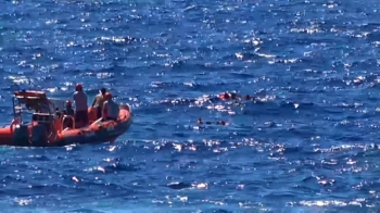 This grab from a video taken by Local Team shows migrants rescued for days by NGO Proactiva Open Arms charity ship, being rescued by a Spanish patrol boat after throwing themselves in the water to try and swim to the nearby Italian island of Lampedusa in a desperate move after days stuck on board, on Tuesday. — AFP