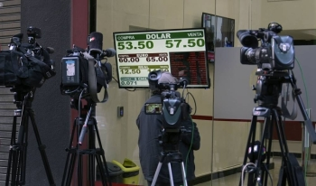 Cameras point at an exchange rate board in the financial district of Buenos Aires on August 20 after Argentina's President Mauricio Macri swore Hernan Lacunza in as the country's new economy minister. — AFP