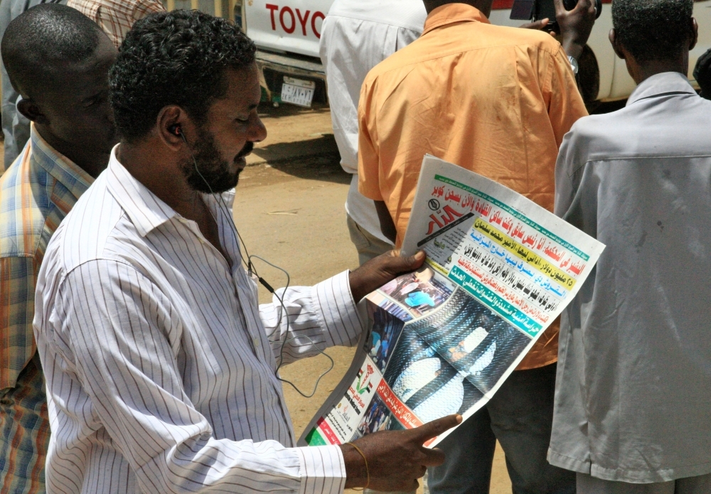 A Sudanese man reads the newspaper on August 20, 2019 headlining the court appearance of Sudan's deposed military ruler Omar al-Bashir during the opening of his corruption trial the previous day. AFP