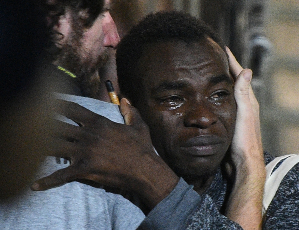A migrant reacts as he disembarks the Spanish rescue ship Open Arms NGO, after it arrived in Lampedusa, Italy, on Tuesday. — Reuters