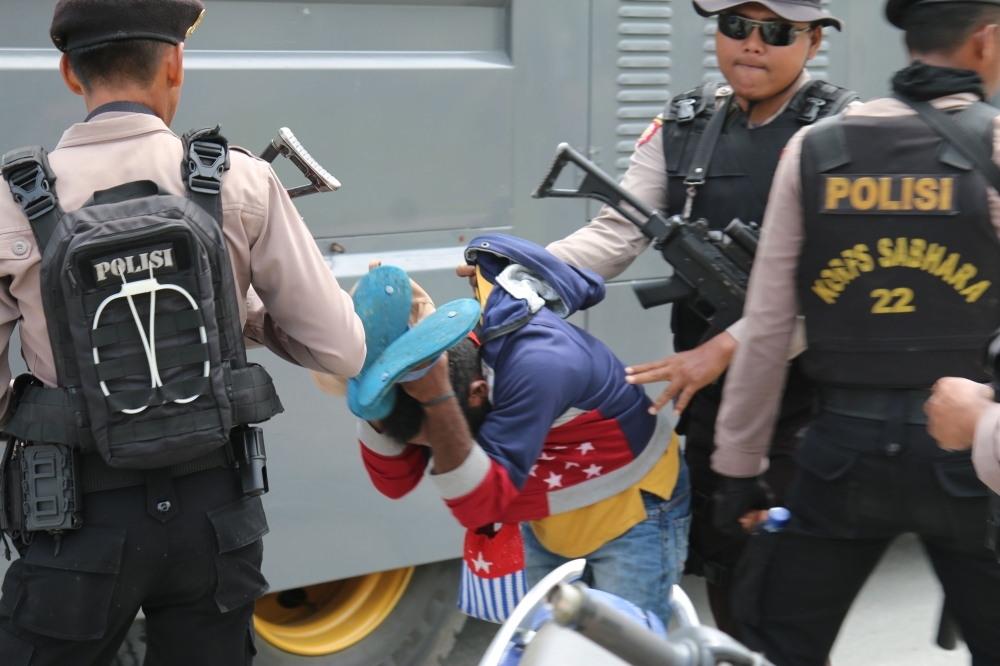 Indonesian policemen detain a Papuan protester in a dispersal operation in Timika on Wednesday. — AFP