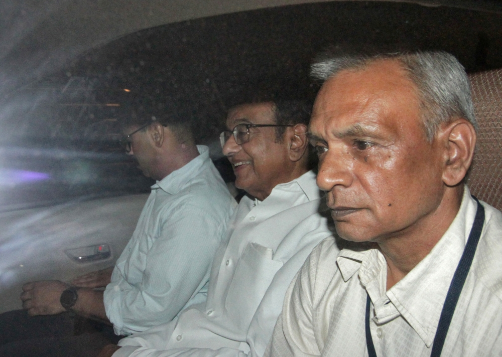 India's former Finance Minister Palaniappan Chidambaram, center, sits in a vehicle after he was arrested by the Central Bureau of Investigation (CBI) officials in his residence in New Delhi, India, on Wednesday. — Reuters
