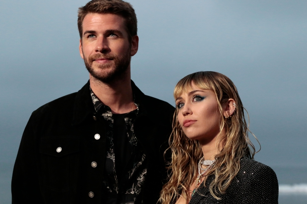 US singer Miley Cyrus and husband Australian actor Liam Hemsworth arrive for the Saint Laurent Men's Spring-Summer 2020 runway show in Malibu, California, in this June 6, 2019 file photo. — AFP