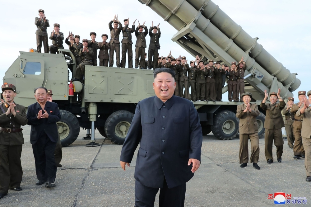 This picture taken on Saturday and released on Sunday by North Korea's official Korean Central News Agency (KCNA) shows North Korean leader Kim Jong Un (C) celebrating the test-firing of a 'newly developed super-large multiple rocket launcher' at an undisclosed location. -AFP
