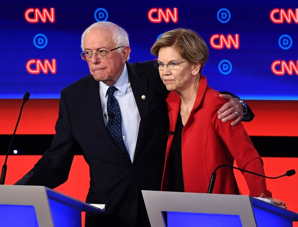 In this file photo taken on July 30, 2019 Democratic presidential hopefuls US Senator from Vermont Bernie Sanders (L) and US Senator from Massachusetts Elizabeth Warren hug after participating in the first round of the second Democratic primary debate of the 2020 presidential campaign season in Detroit, Michigan. -AFP