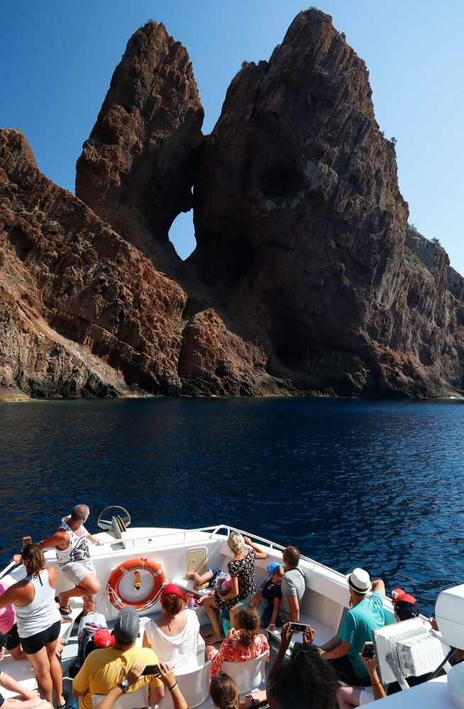Tourists take a cruise on August 19, 2019, in the Scandola Nature Reserve, on the western coast of the French Mediterranean island of Corsica. -AFP