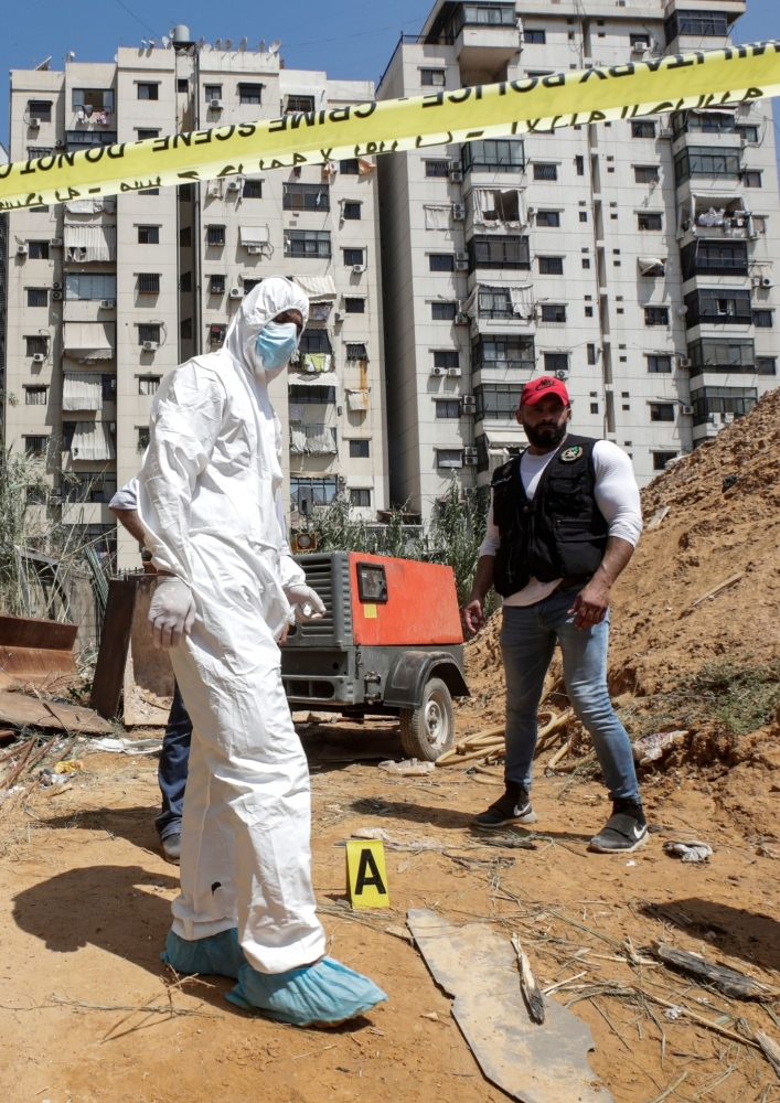 Forensic investigators of Lebanon's military intelligence inspecting the scene where two drones came down in the vicinity of a media center of the Shiite Hezbollah movement in Beirut, Sunday. — AFP