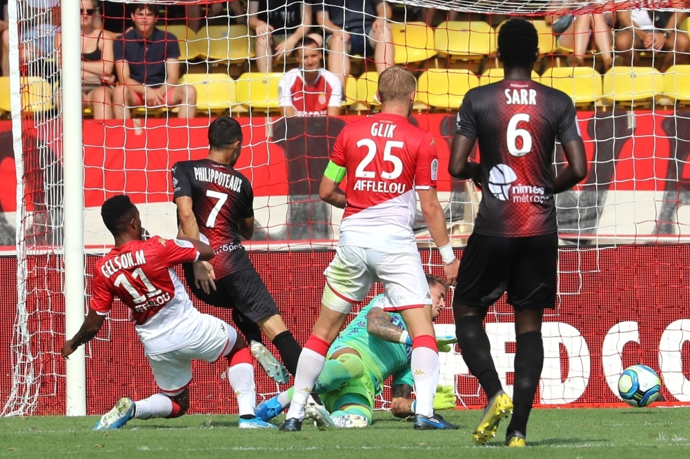 Nimes' French forward Romain Philippoteaux (2nd L) scores a goal during the French L1 football match Monaco vs Nimes at the