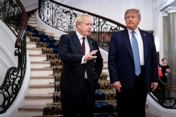 US President Donald Trump (R) and Britain's Prime Minister Boris Johnson speak before a working breakfast at the G7 Summit in Biarritz, France on Sunday. -AFP