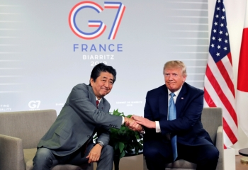 US President Donald Trump and Japan's Prime Minister Shinzo Abe shake hands as they attend a bilateral meeting during the G7 summit in Biarritz, France, on Sunday. -Reuters