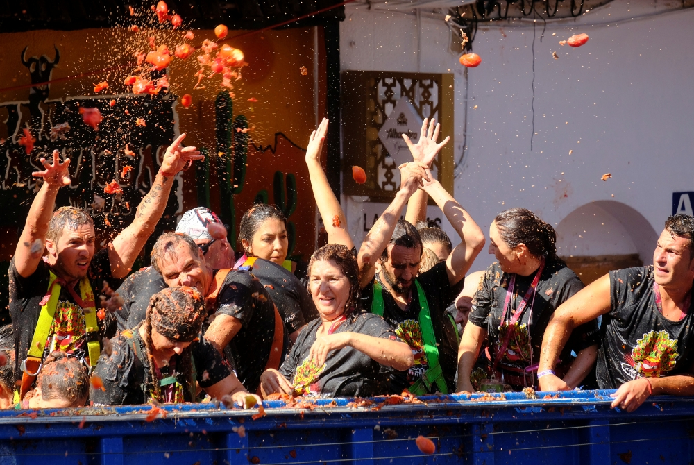 Revelers on a truck throw tomatoes into the crowd during the annual