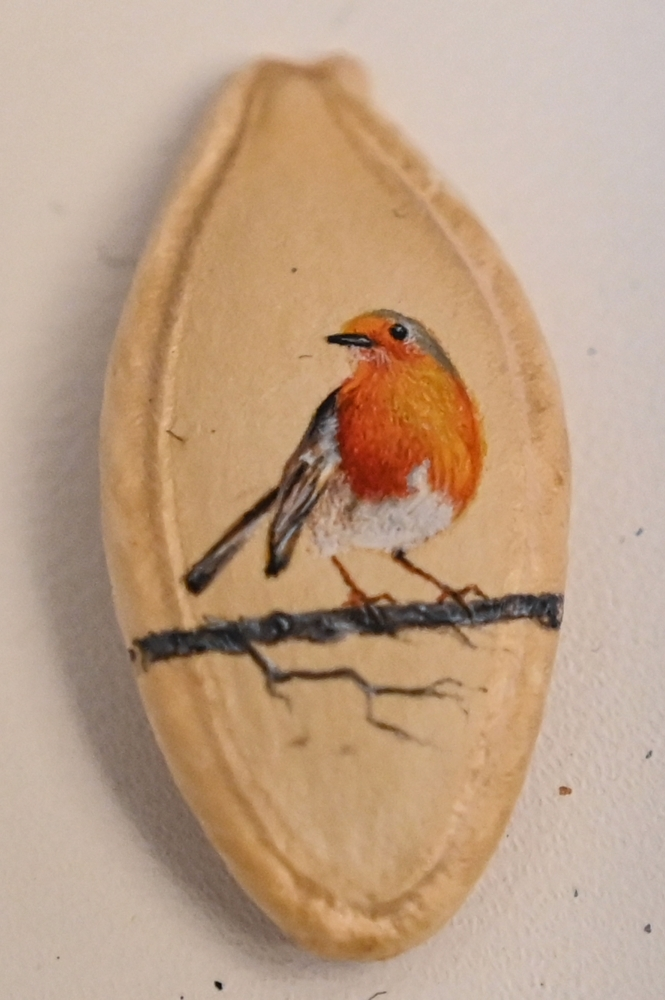 A picture taken on August 23, 2019 shows a bird painted on a pumpkin seed by Turkey's micro artist Hasan Kale in Istanbul. -AFP