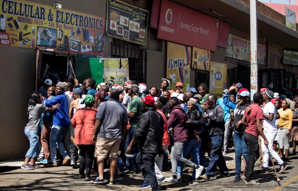 South African looters take items from an alleged foreign-owned shops during a riot in the Johannesburg suburb of Turffontein on Monday. -AFP