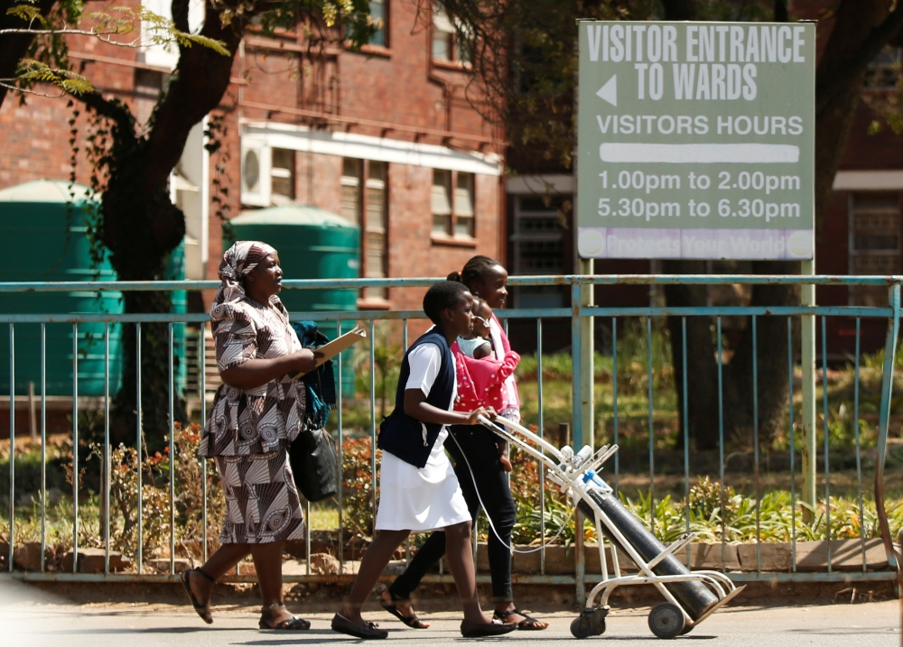 A nurse assisits a mother and her child outside Harare Central Hospital as the country's public sector doctors began a strike in Harare, Zimbabwe, on Tuesday. — Reuters