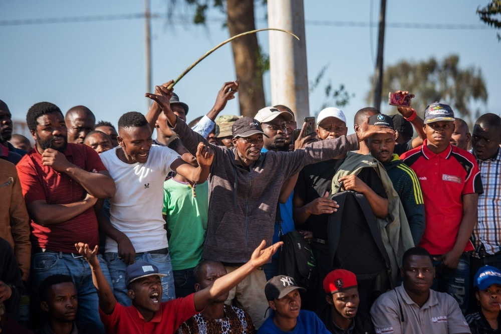 Zulu residents of the Jeppe Men Hostel scream waving batons in the Johannesburg CBD on Tuesday after South Africa's financial capital was hit by a new wave of anti-foreigner violence. -AFP