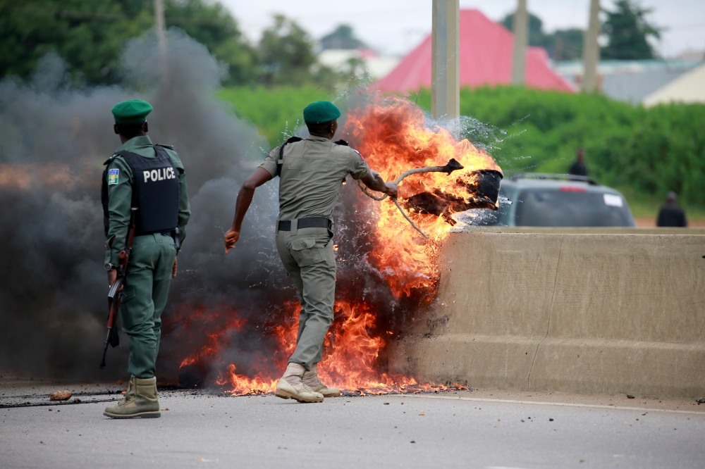 A police office removes burning tires from the road, as protesters set up fires to block traffic along Airport Road in Abuja, Nigeria, on Wednesday. — Reuters