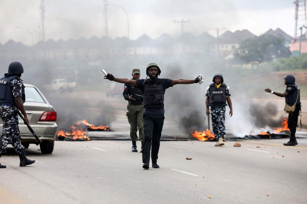 Anti-riots policemen try to calm down protestors during a demonstration and attacks against South Africa's owned shops in Abuja, Nigeria, on Wednesday. — AFP