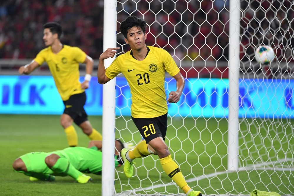 Malaysia's Muhammad Syafiq Ahmad (R) celebrates after scoring a goal during FIFA world cup preliminary qualification round 2 at the Gelora Bung Karno stadium di Jakarta on Thursday. — AFP