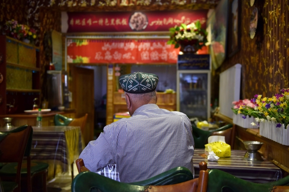 A Uighur man sits in a restaurant in Hotan in China's northwest Xinjiang region in this May 30, 2019 file photo. — AFP