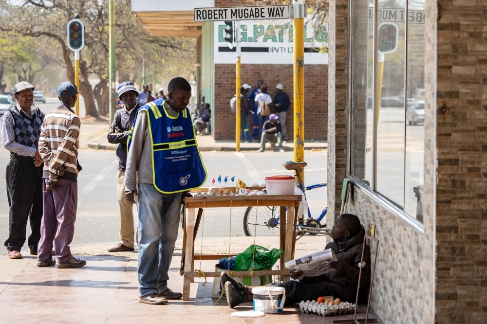 Two men chat along a side walk in Bulawayo on Friday, on the corner of the 'Robert Mugabe Way' street. — AFP