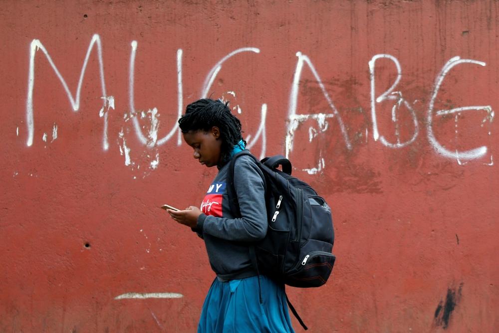 A woman walks past a wall where it's written