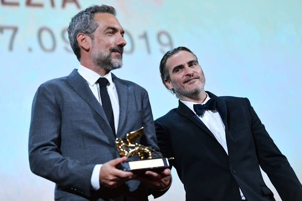 US director Todd Phillips (L), flanked by US actor Joaquin Phoenix, holds the Golden Lion award for Best Film he received for the movie