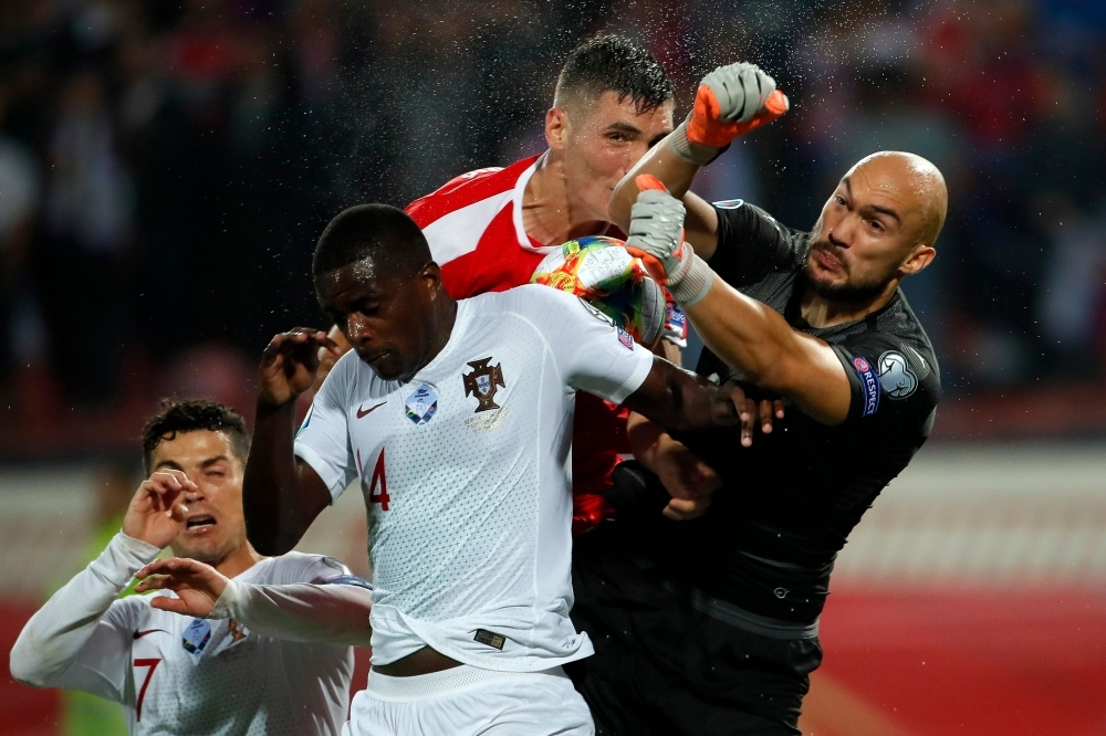 Portugal's William Carvalho (2ndL) vies with Serbia's goalkeeper Marko Dmitrovic (R) during the Euro 2020 football qualification match between Serbia and Portugal in Belgrade, on Saturday. — AFP