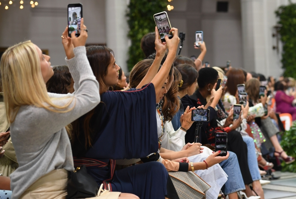 Guests use their mobile phones during the Tory Burch Spring/Summer 2020 show during New York Fashion Week: The Shows at the Brooklyn Museum in New York City on Sunday. — AFP