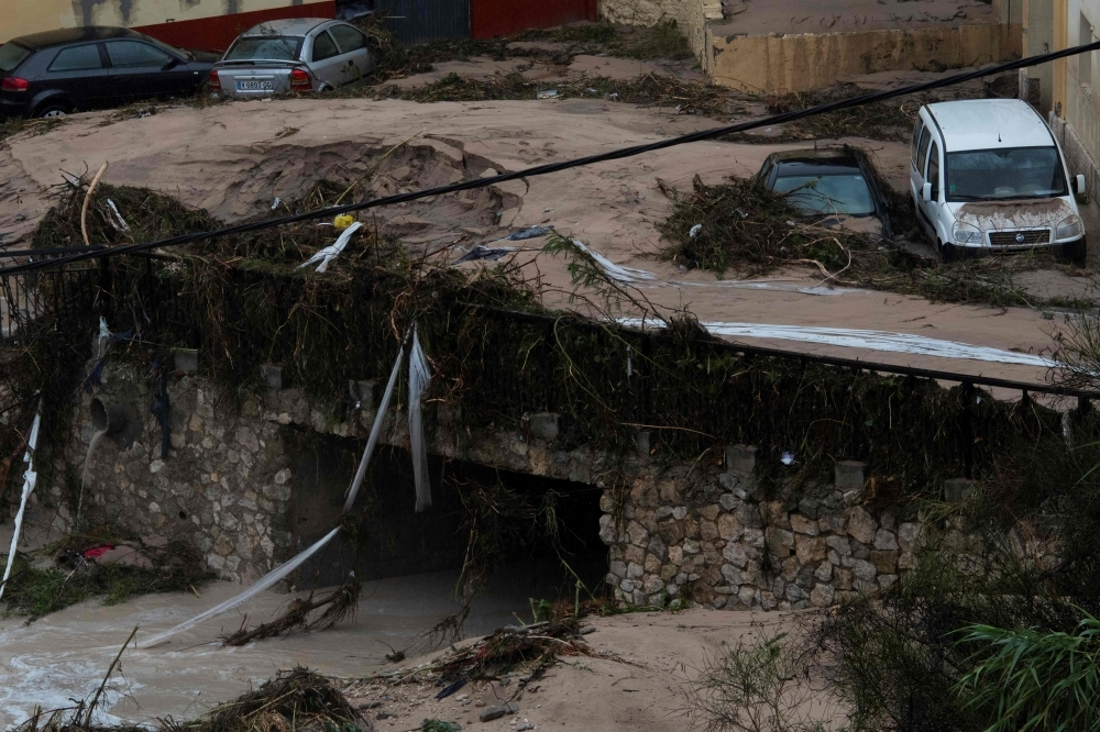 Damages cars are pictured after a street was flooded in Ontinyent on Thursday as torrential rains hit southeastern Spain overnight, sparking major flooding in the Valencia region and closing schools in a move affecting a quarter of a million children. — AFP