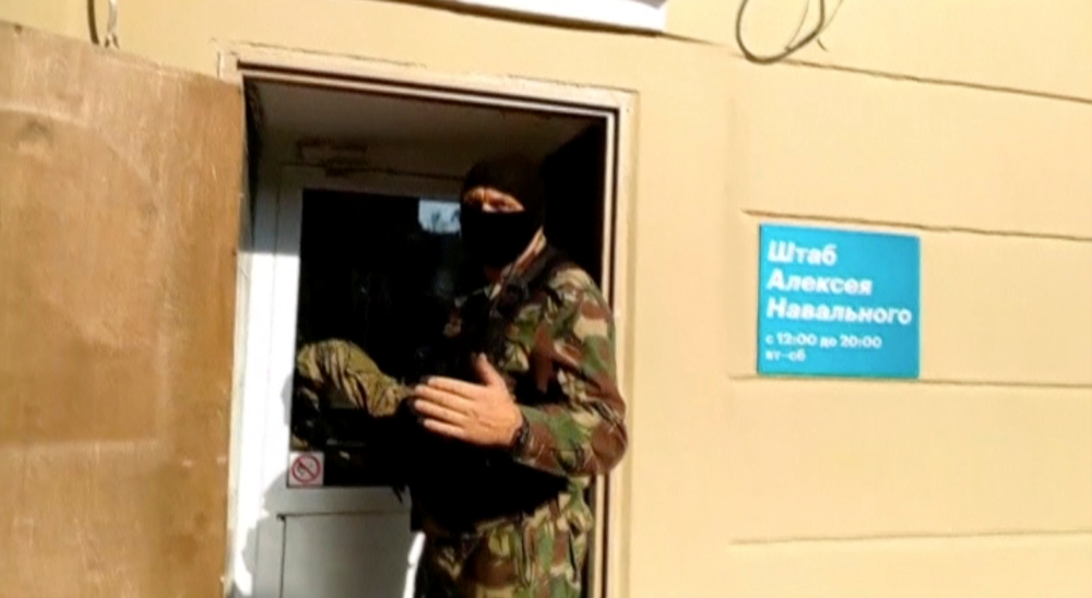 A still image taken from a video footage shows a masked law enforcement officer addressing journalists during a raid in a local office of Kremlin critic Alexei Navalny in Perm, Russia, on Thursday. — Reuters