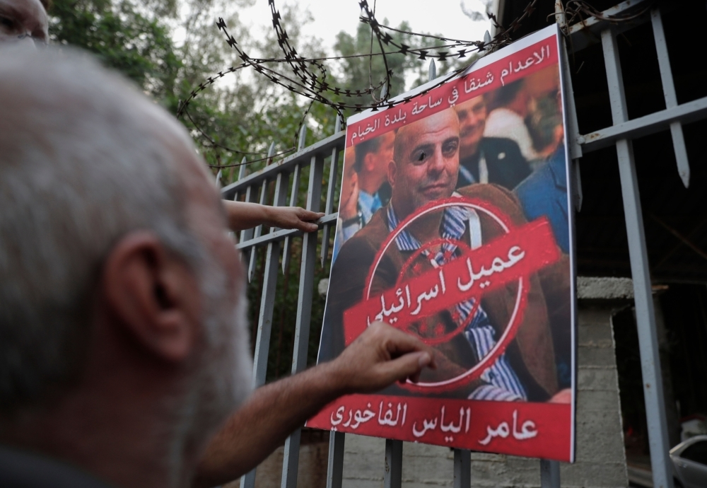 A man formerly detained by the pro-Israel South Lebanon Army (SLA) militia reacts toward a poster depicting former SLA member Amer Al-Fakhoury, during a demonstration denouncing his return and entry outside the Justice Palace in the Lebanese capital Beirut, on Thursday. — Reuters