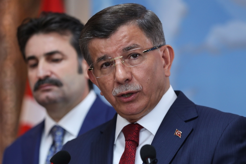 Former Turkish Prime Minister Ahmet Davutoglu, right, holds a press conference at his office in Ankara on Friday to announce that he would launch a