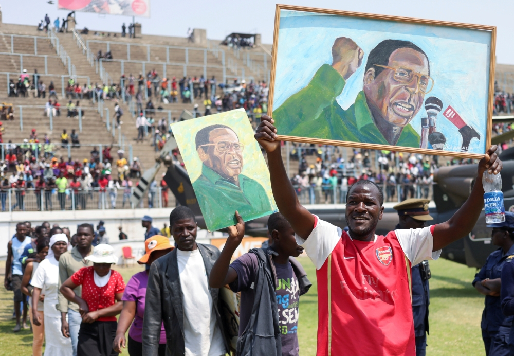 Mourners hold paintings with the face of former Zimbabwean President Robert Mugabe, as they queue to pay their last respects as he lies in state at the at Rufaro stadium, in Mbare, Harare, Zimbabwe, on Friday. — Reuters