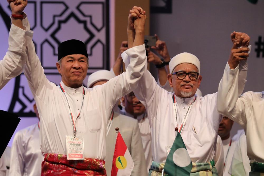 United Malays National Organization (UMNO) President Ahmad Zahid Hamidi (L) and Pan-Malaysian Islamic Party (PAS) President Hadi Awang hold hands during Ummah Unity Gathering in Kuala Lumpur, Malaysia, on Saturday. -Courtesy photo