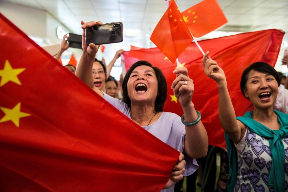 Pro-China supporters sing the national anthem inside a shopping mall in the Kowloon Bay district of Hong Kong on Saturday. -AFP