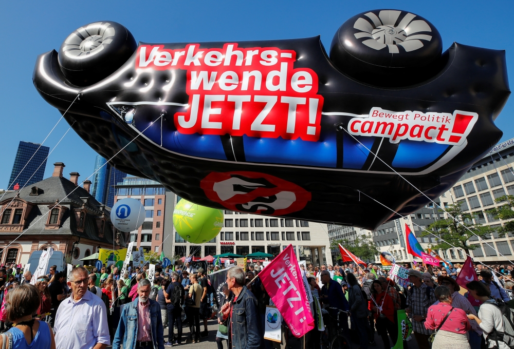 People stand under an inflatable car with a sign reading