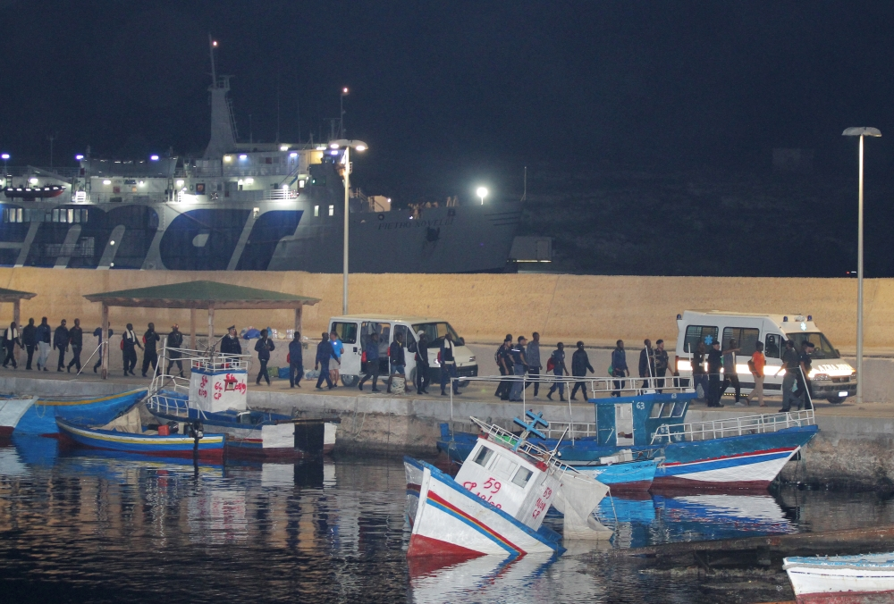 Migrants walk towards vehicles at the port in Lampedusa after the Italian government allowed the disembarkation of 82 migrants on board the rescue ship Ocean Viking, on Saturday. -Courtesy photo