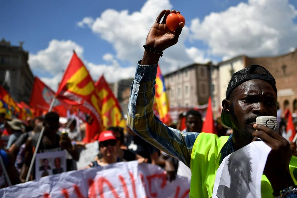 In this file photo taken on June 16, 2018 in Rome, a demonstrator raises a tomato in the air during a march organized by Italy's USB (Base Union of Trade Unions). -AFP