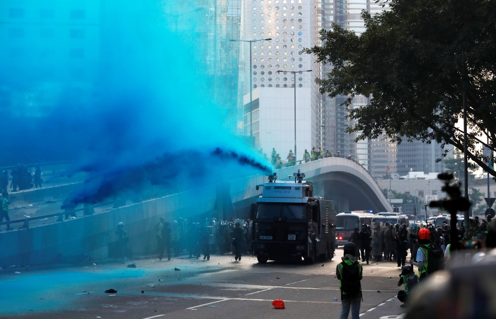 Police vehicle sprays blue-colored water towards anti-government protesters during a demonstration near Central Government Complex in Hong Kong on Sunday. -Reuters