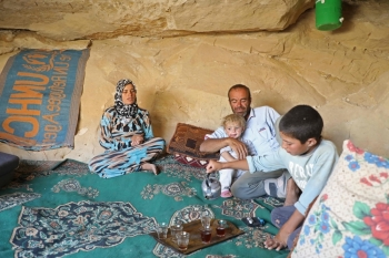 Abu Ahmad, a displaced Syrian from Termala sits with his family inside a cave he dug for shelter in the village of Kafr Lusin near the Syria-Turkey border, on September 9, 2019. -AFP