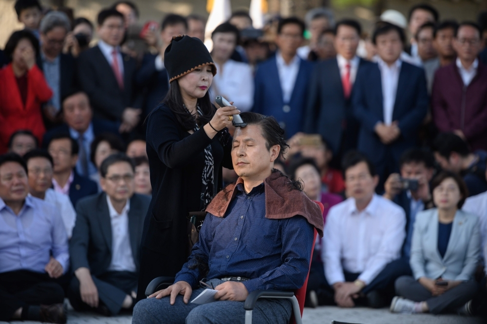 Main opposition Liberty Korea Party leader Hwang Kyo-ahn, center, has his head shaved during a protest outside the presidential Blue House in Seoul on Monday. — AFP