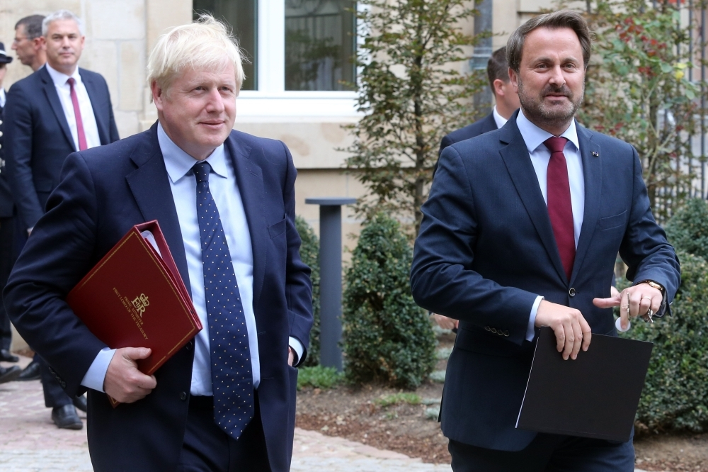 British Prime Minister Boris Johnson, left, and Luxembourg's Prime Minister Xavier Bettel, right, leave a meeting with EU Commission President and officials in Luxembourg on Monday. — AFP